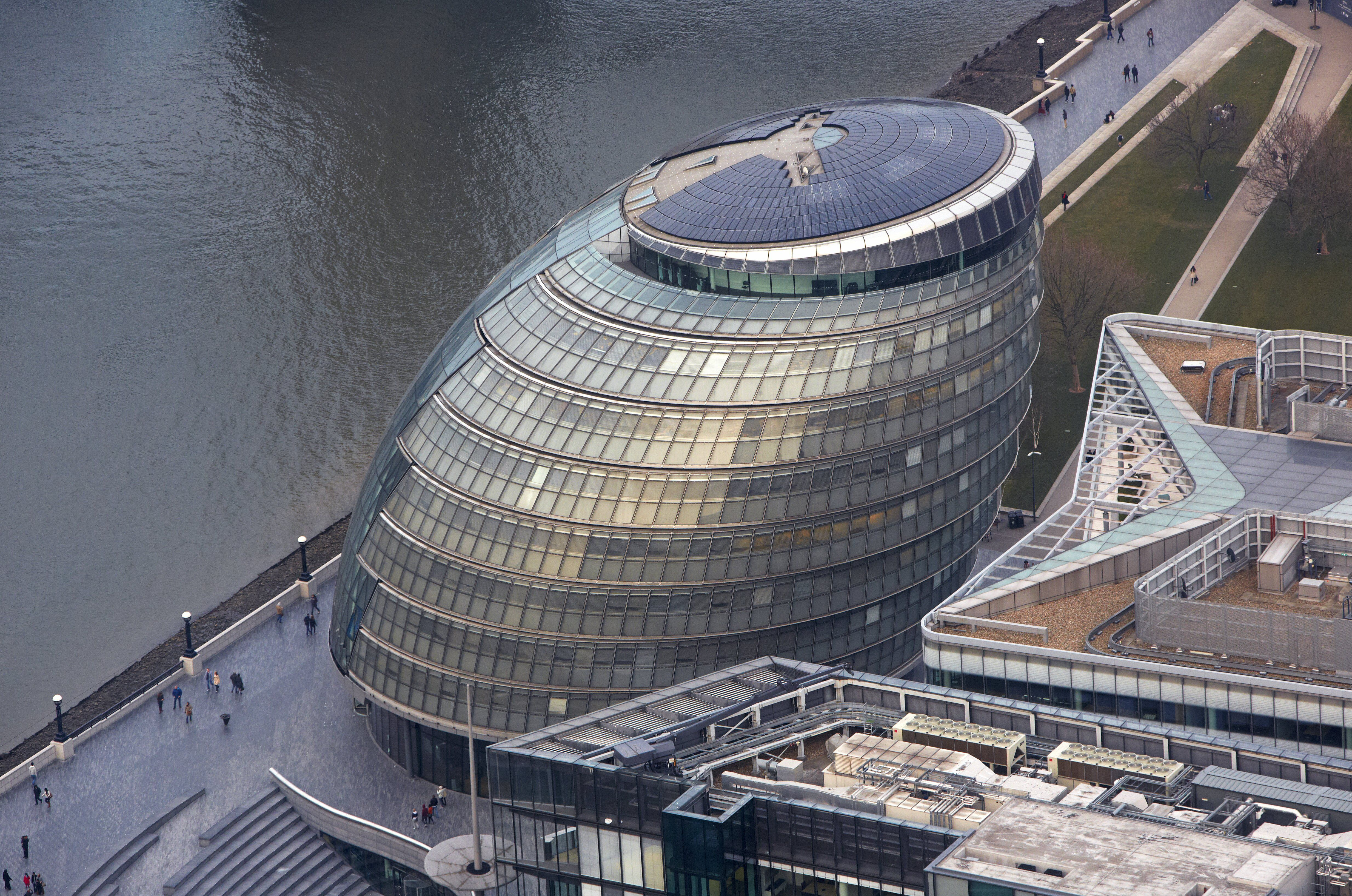 Elevated view of slanted Slinky-like building near a river