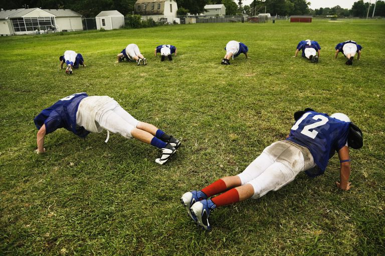 American football team doing push ups on sport field, Virginia, USA