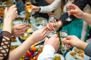 People hands Clinking glasses with vodka and wine