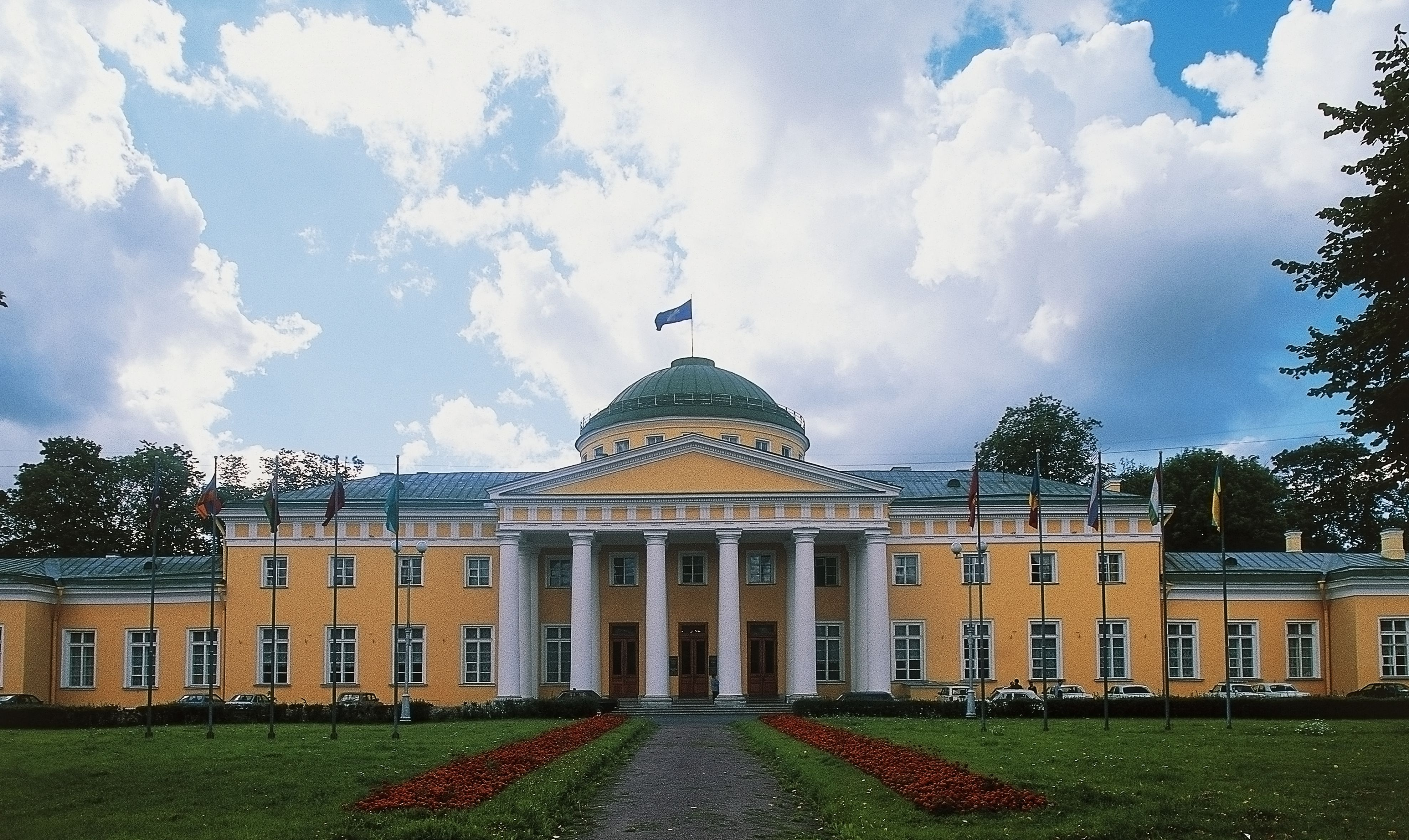 horizontal-orientation palace, yellowish facade, central columns with pediment and dome
