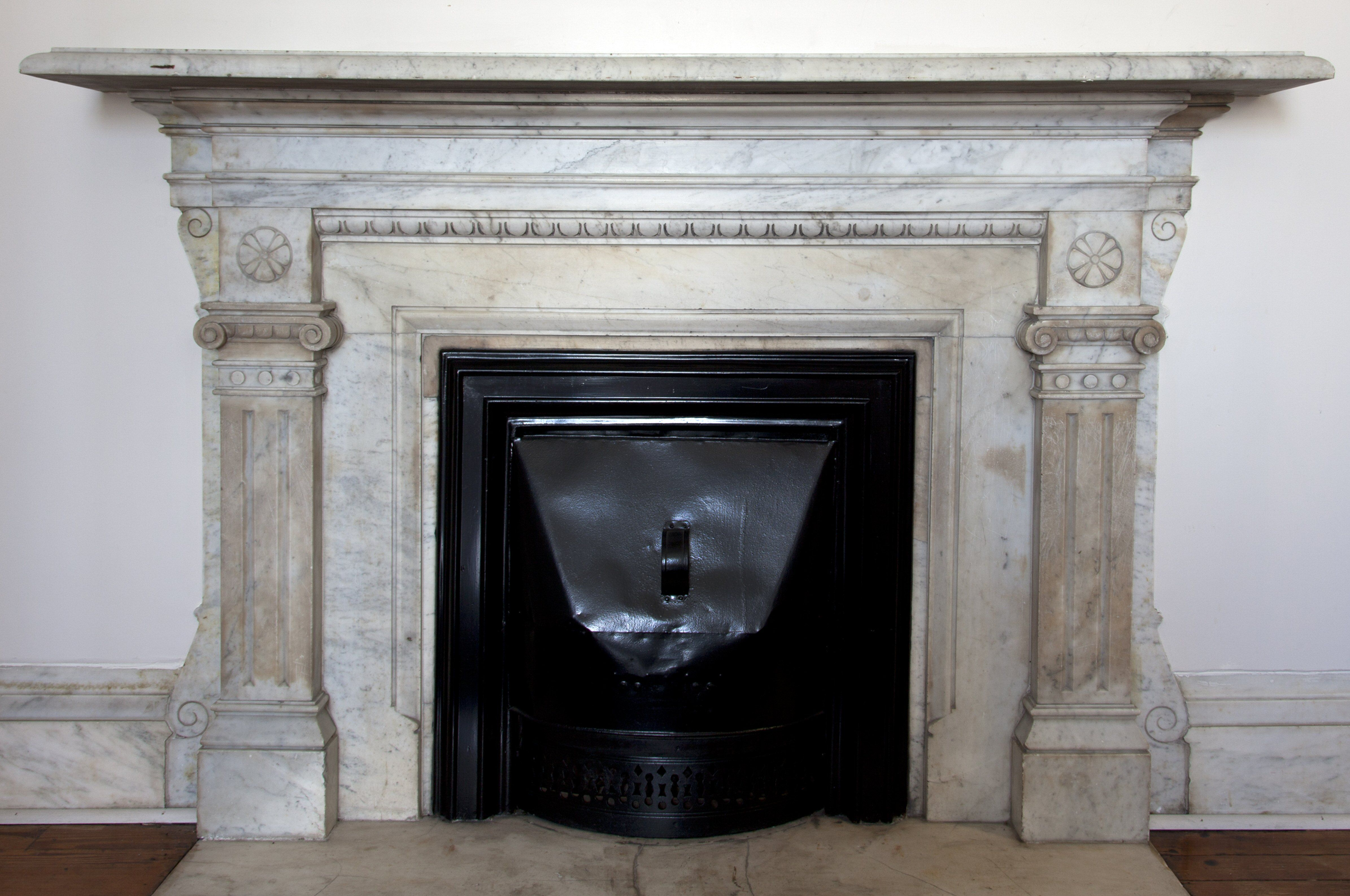 marble fireplace with two classical pilasters on either side of the opening and below the mantle