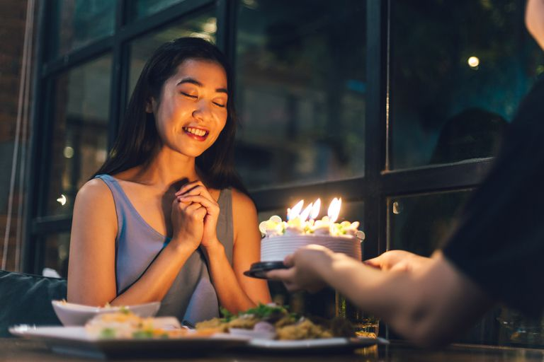Asian women pray from her birthday cake in the night of happiness. - stock photo