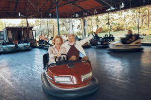 playful senior couple having fun together driving bumper car