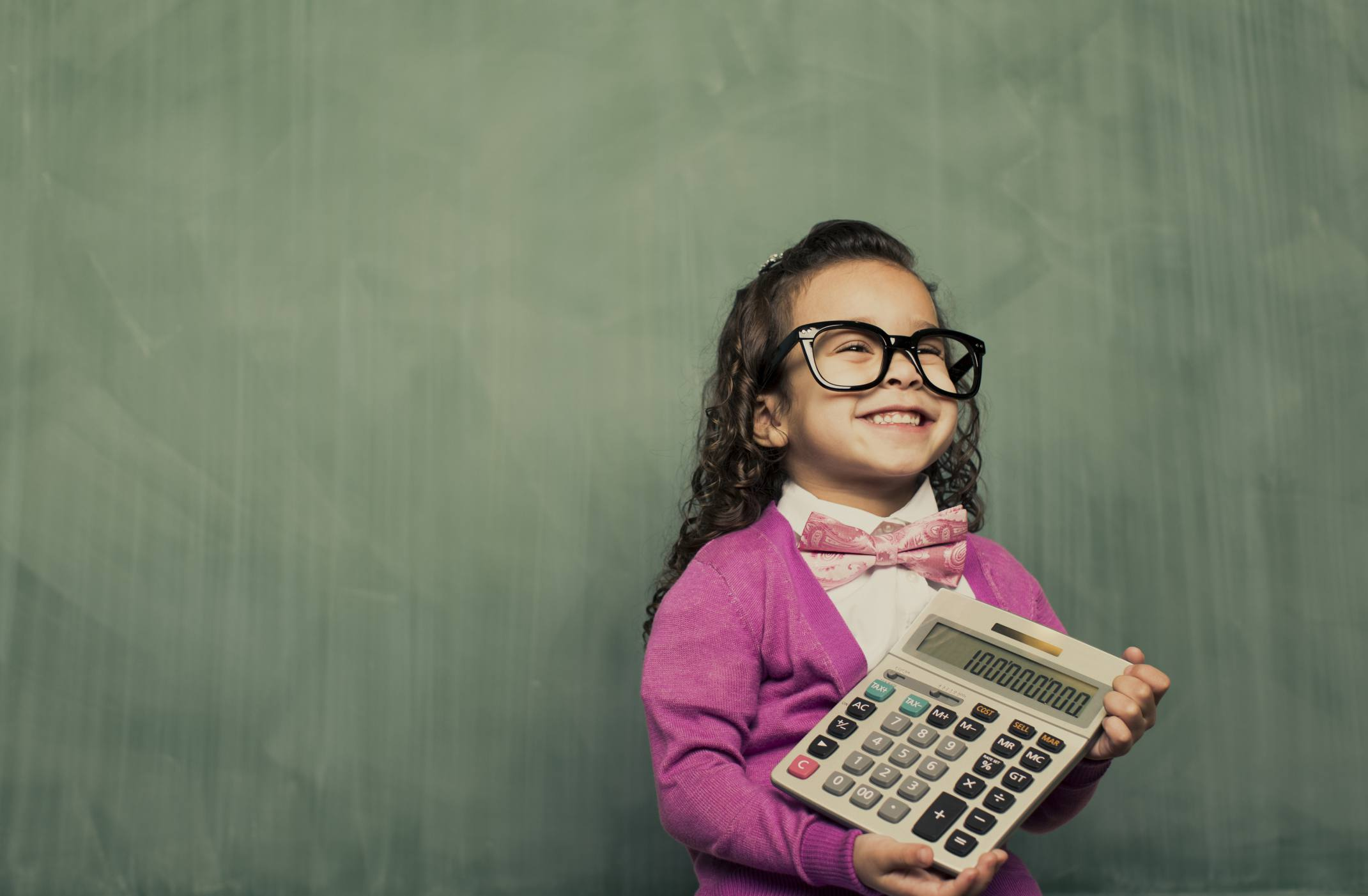 A young girl holding a large calculator.