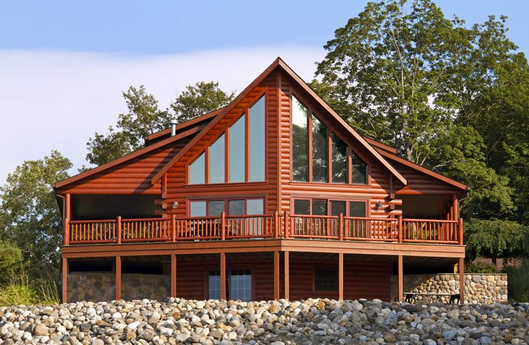 Contemporary log home, with gable of glass and facade-wide porch