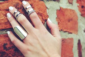 Hand with metal rings resting against a brick structure.