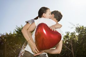 A hugging couple with a heart-shaped balloon
