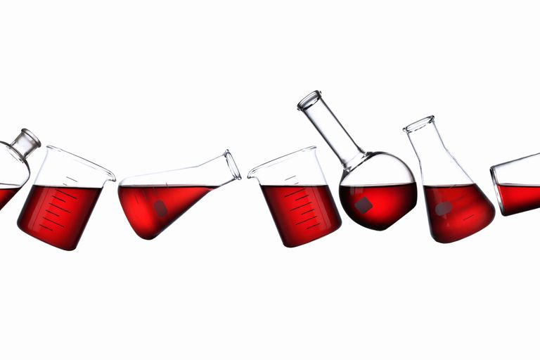 scientific glassware partially filled with red liquid, floating at various angles