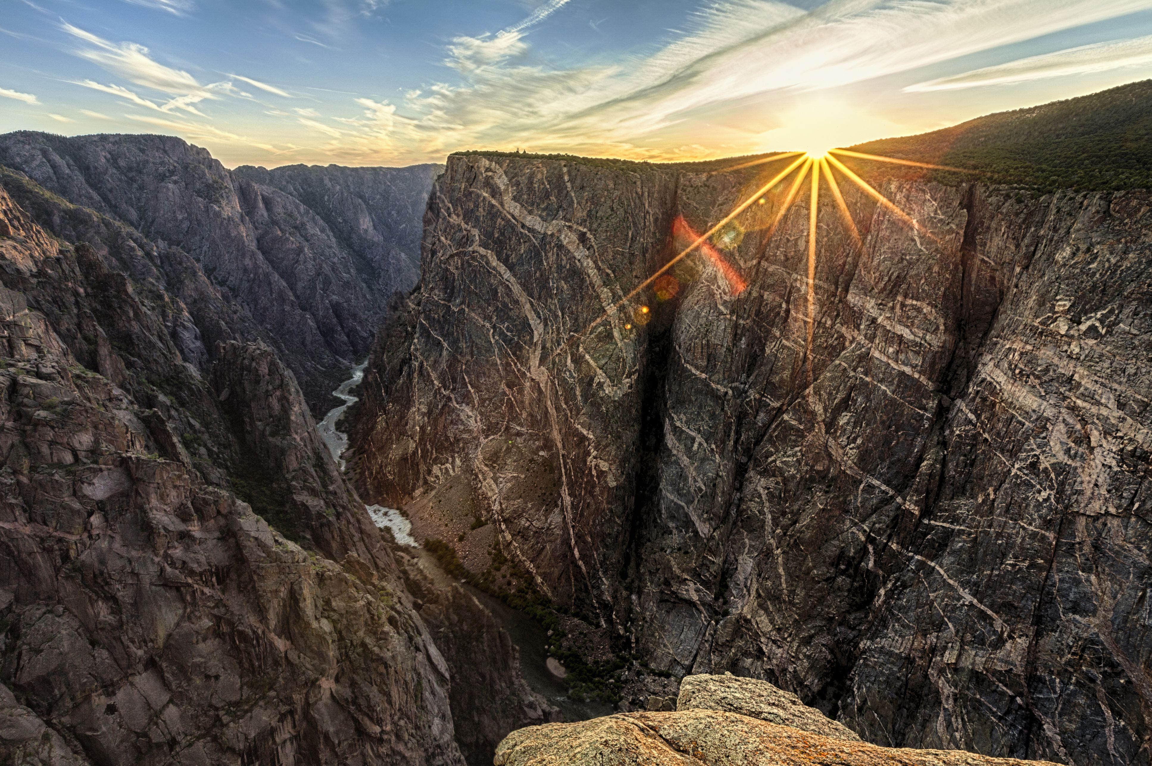 Black Canyon of the Gunnison is a National Park in Colorado, known for pink pegmatite. Pegmatite forms pale bands in the cliffs.