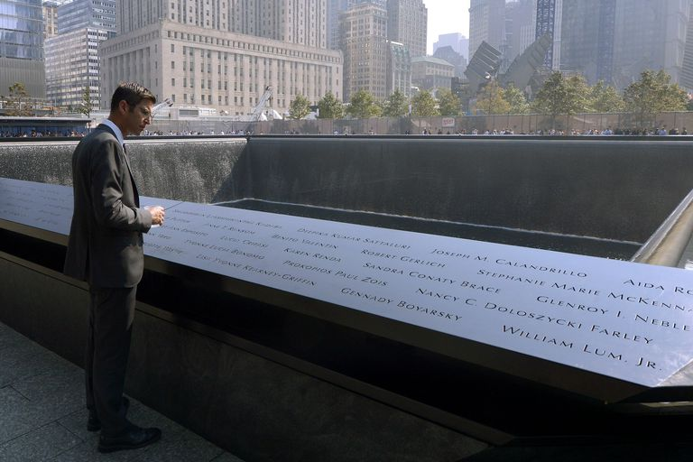 man in suit stands reading names in stone that surrounds a reflecting pool