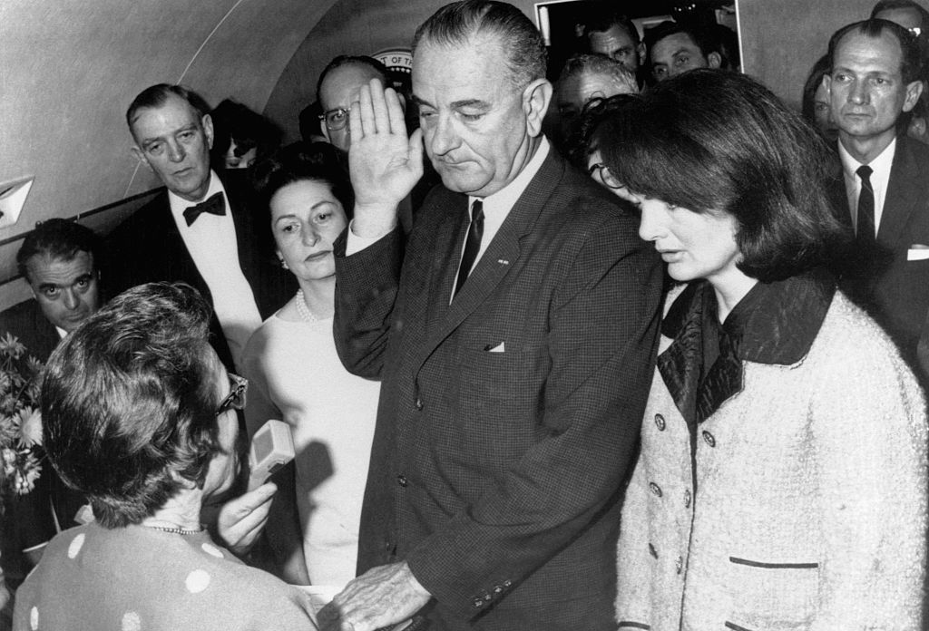 Vice President Lyndon B. Johnson is sworn in to the office of the Presidency aboard Air Force One in Dallas, Texas, hours after the assassination of President John F. Kennedy.