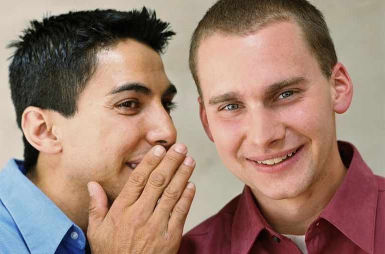 Young man whispering to friend
