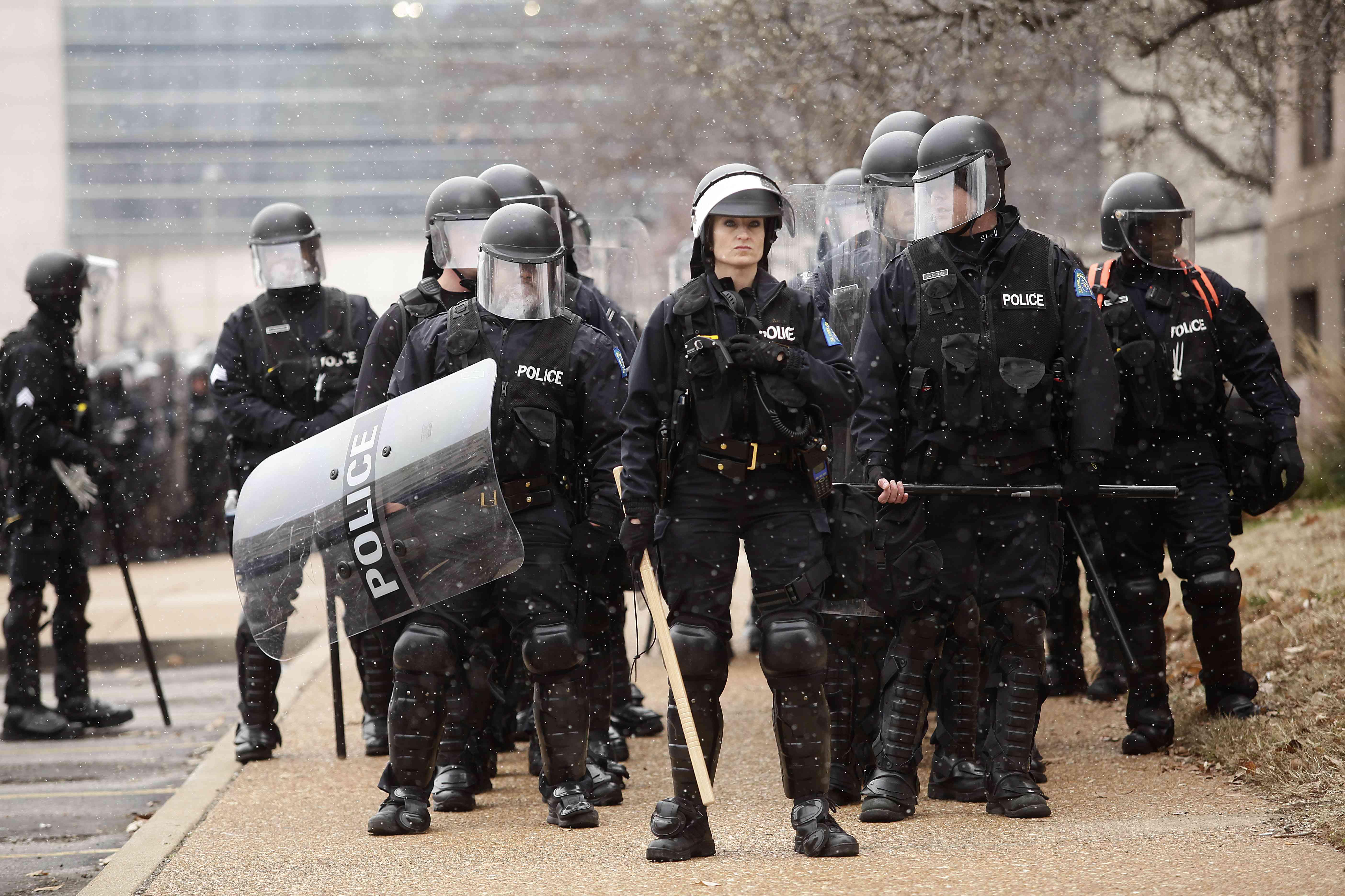 Polizisten in Schutzkleidung stehen vor dem Rathaus, als Demonstranten gegen den Tod von Michael Brown in Ferguson, Missouri, protestieren.