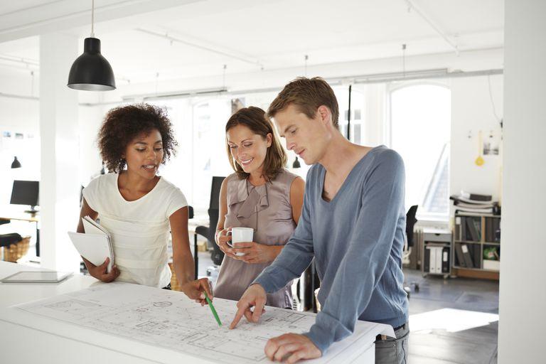 Tres jóvenes platicando sobre información en un plano.
