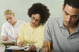 Three college students in taking notes from a textbook in class