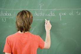 Student writing Spanish on a blackboard