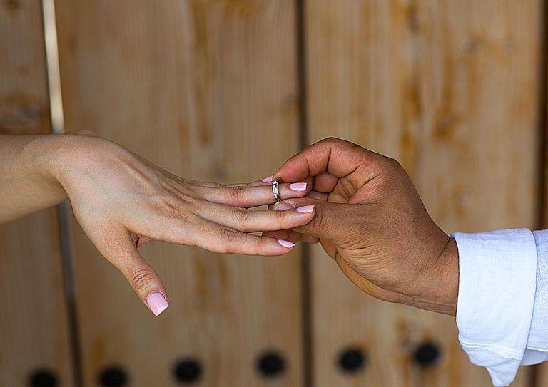 Mano de varón introduciendo alianza matrimonial en dedo de mujer.