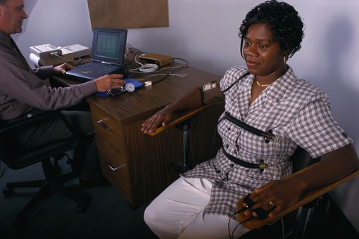 A woman hooked up to polygraph equipment