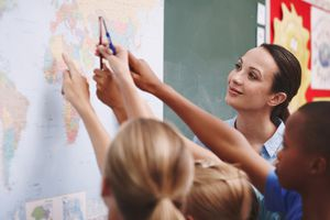 A teacher oversees students pointing out countries on a world map