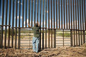 Migrante en la verja fronteriza entre México y Estados Unidos