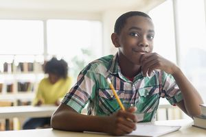 Student thinking in class while writing in journal