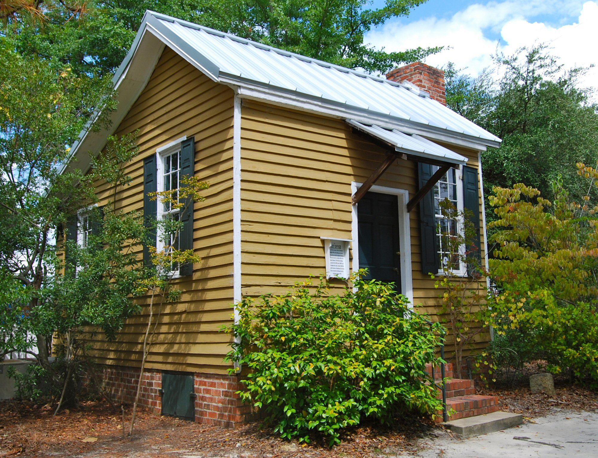 Photo of a small building, a modified saltbox, deep gold with white trim and very dark shutters.