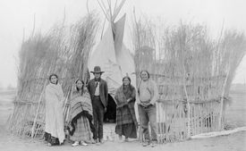 Five Arapaho Indians, standing outside a tipi surrounded by a brush fence, November 18, 1904.