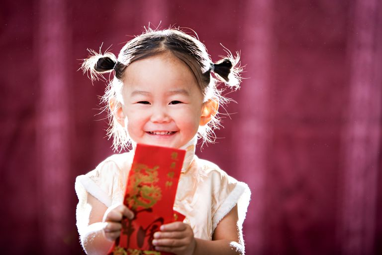 Little girl holding red envelope for Chinese New Year.