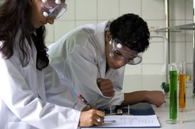 Two students writing a report for an experiment performed in a chemical laboratory.