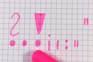 Punctuation Marks written in pink pen on square paper