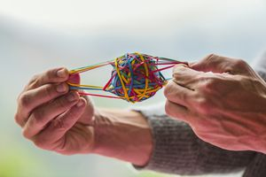 A rubber band stretches and returns to its original shape, displaying elasticity.