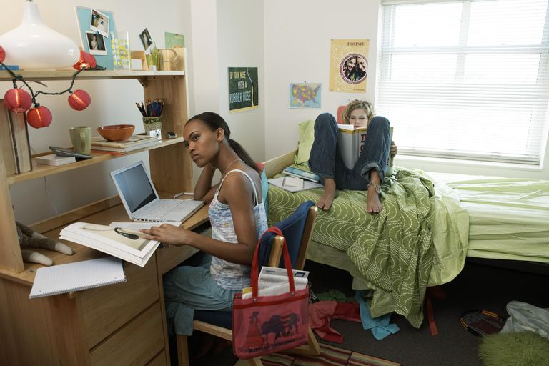 Two young women in student dorm, one sitting on bed, other at desk