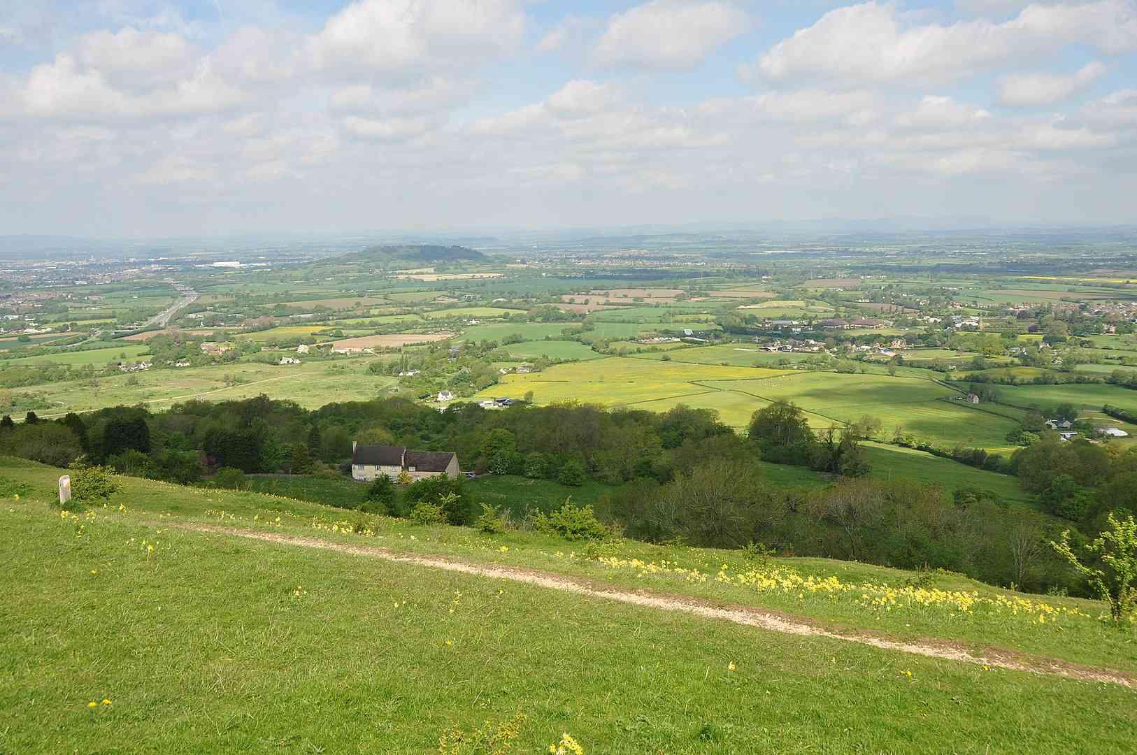 Crickley Hill an einem sonnigen Tag mit Feldern und Häusern im Hintergrund.