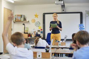 Kid raising his hand in a classroom