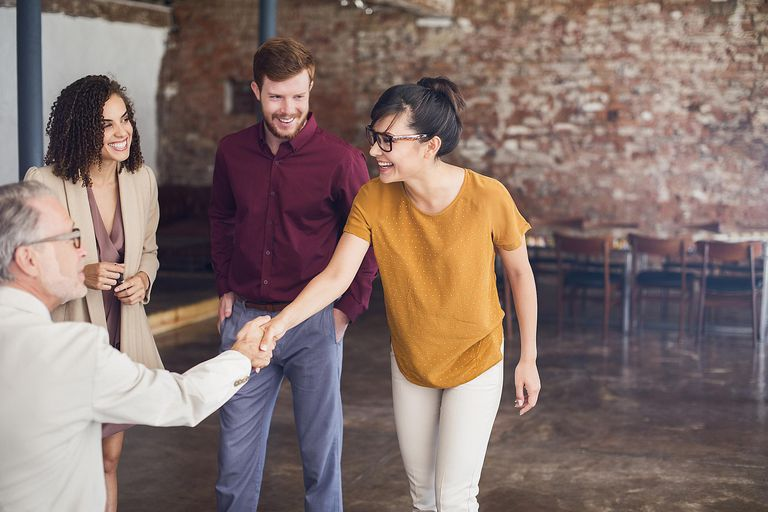 Happy business people shaking hands in creative office