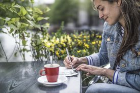 Woman writing postcards in a street cafe