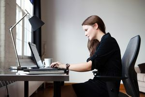 Businesswoman in an office working on a laptop computer