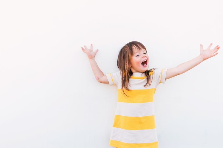 Young girl with arms stretched out and mouth open against a white background.