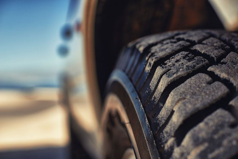 Closeup of a vehicle tire with sand on the treads