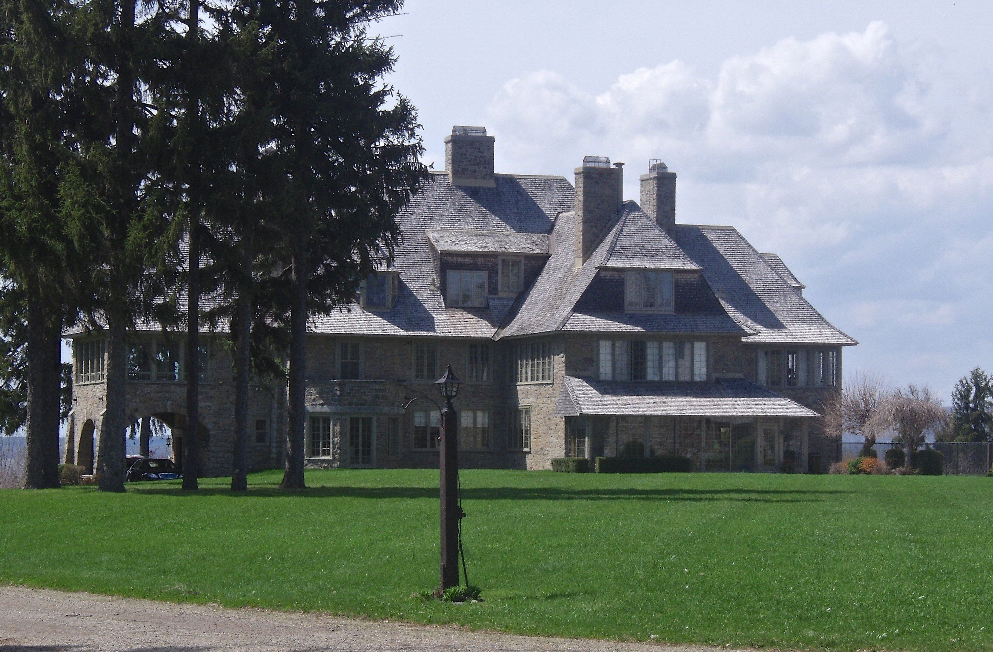 Stone shingle estate, shed dormers, multiple chimneys, gables, car port, set back from road overlooking water