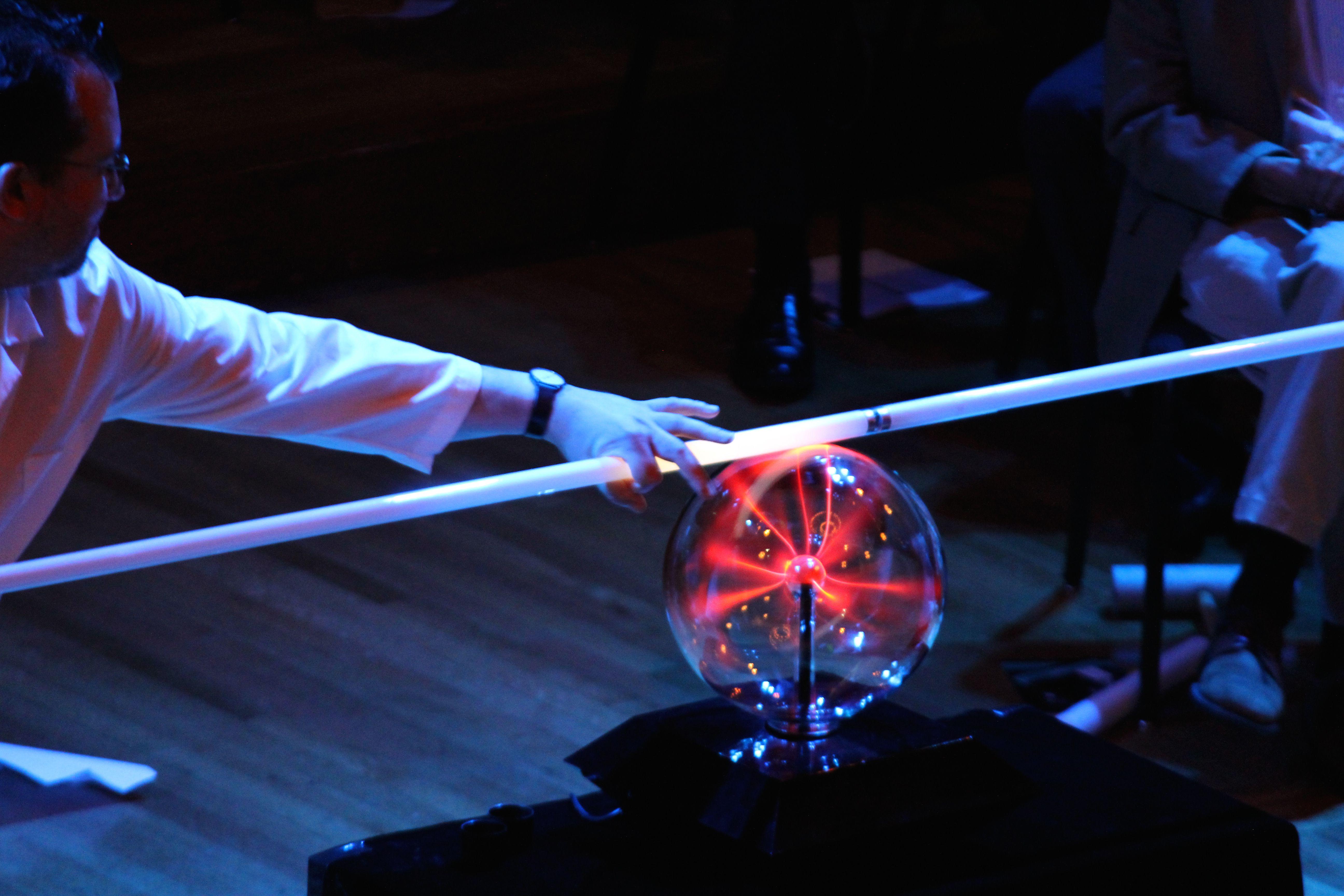 man using fluorescent light with a plasma ball