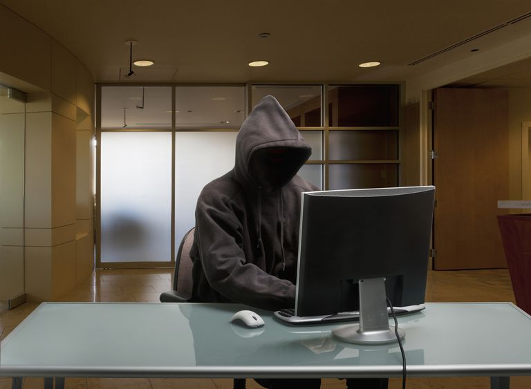 Hooded figure on a library computer