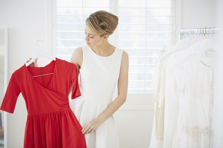 woman looking at red dress in closet
