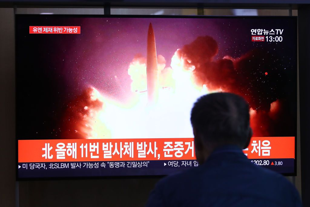 People watch a TV showing a file image of a North Korean missile launch.