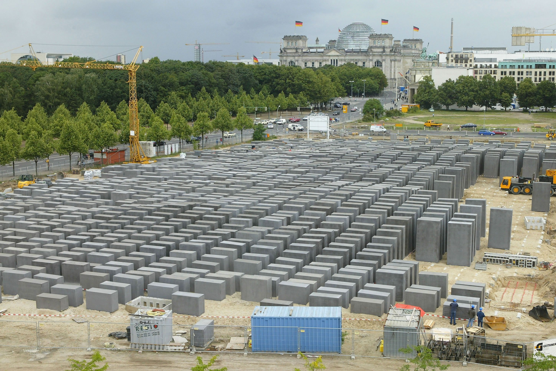 chantier de construction avec des grues et des ouvriers plaçant des dalles de pierre individuelles dans un champ