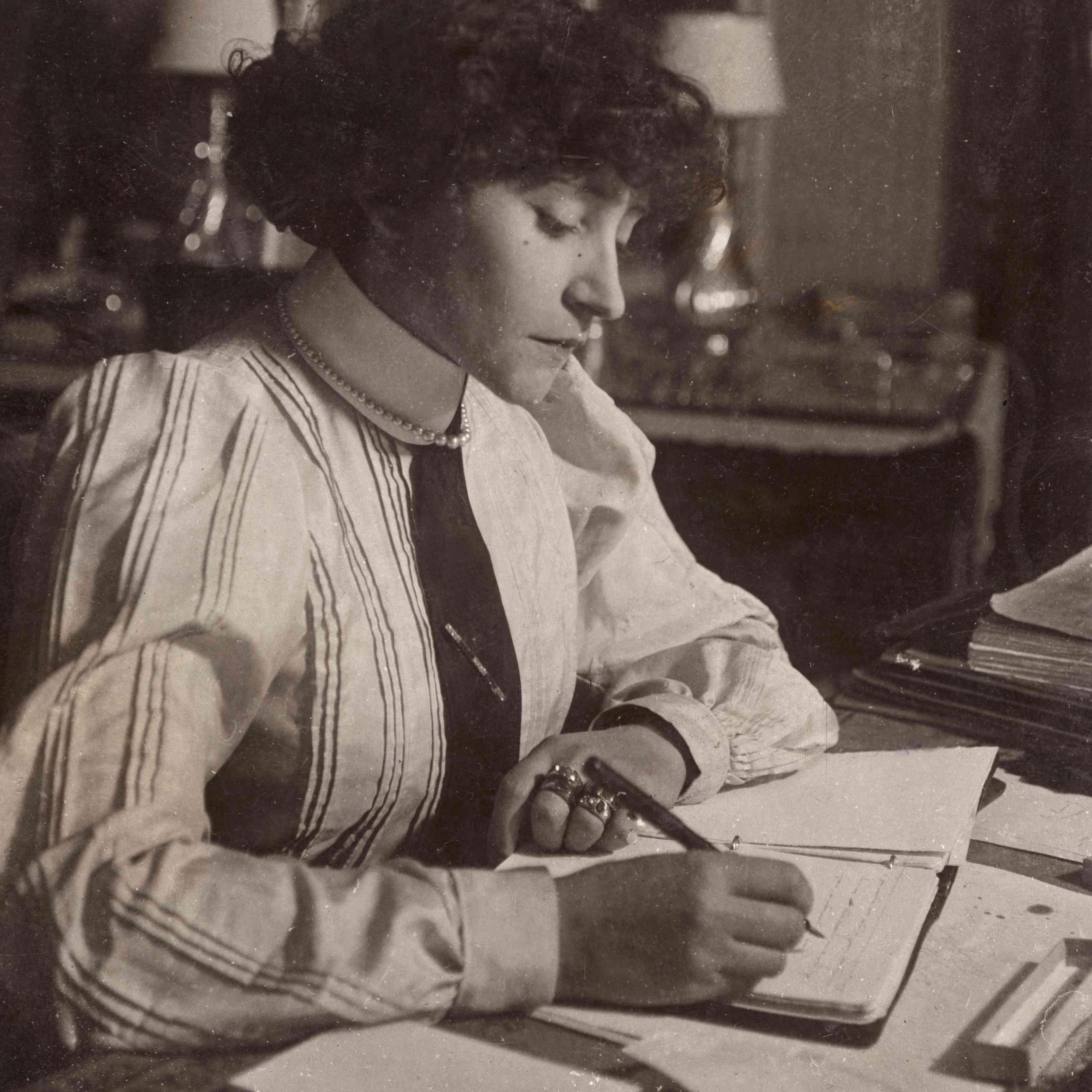 Colette con un vestido de manga larga escribiendo en un cuaderno