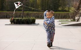 A toddler plays with a kite in a park in Xian, China