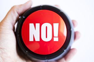 hand holding large button that says No!