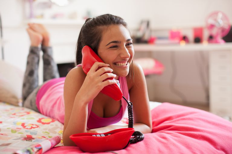Teenage girl talking on telephone in bedroom
