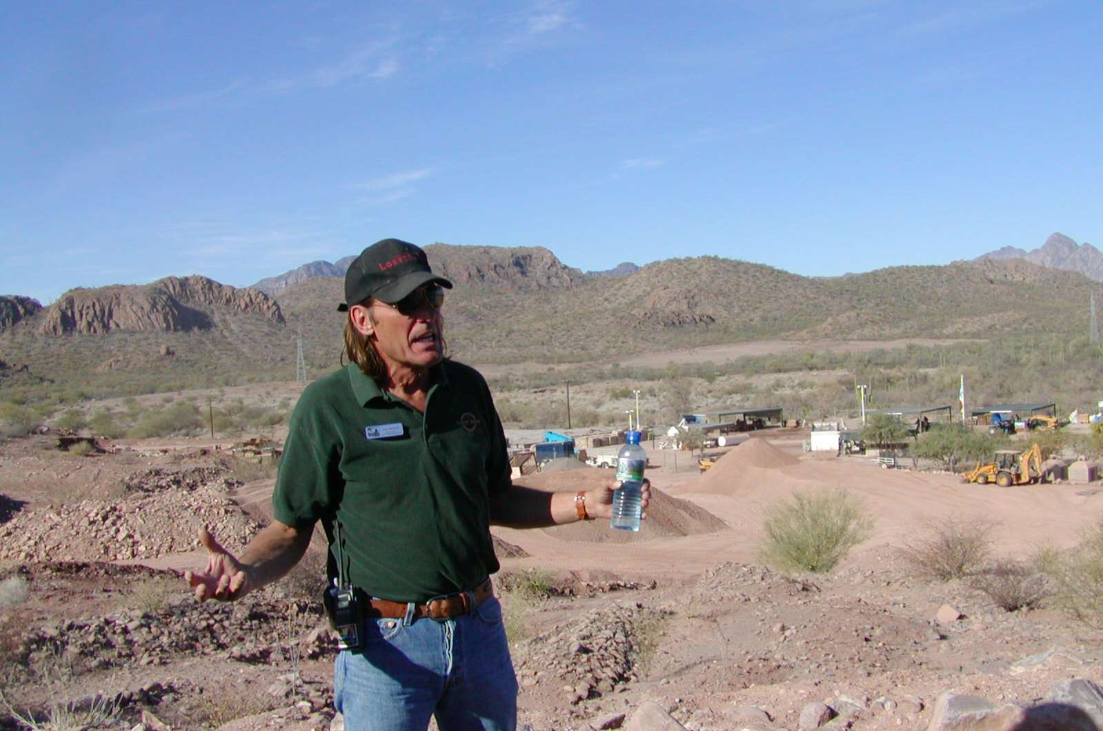 white man, long hair, gesturing with water bottle in a sandy, mountainous environment